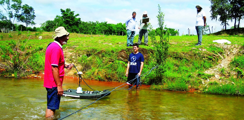 Pedro Rocha e Oátomo Modesto operam o equipamento na água enquanto os técnicos aferem as medições no computor, na margem.